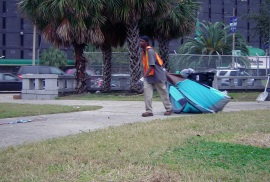 City contracted waste removal employees dragged any remaining tents and belongings into trash compactors, clearing the plaza, which earlier had been filled with hundreds of homeless.