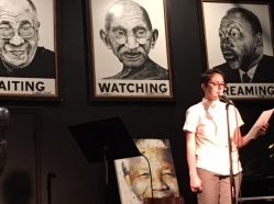 Tanya in white button-down shirt in front of a microphone holding a piece of paper, reading a poem on a black stage, portraits of Dalai Lama, Gandhi, and MLK behind her